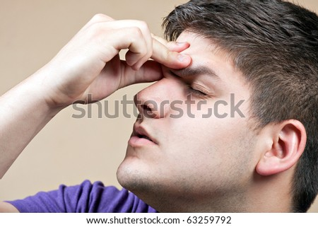 Young man has an intense headache. He might be experiencing stress during a time of economic crisis or other hardship. - stock photo