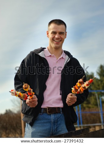 Young man has control over a shish kebab outdoor - stock photo