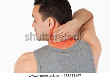 Young man having a back pain against a white background - stock photo
