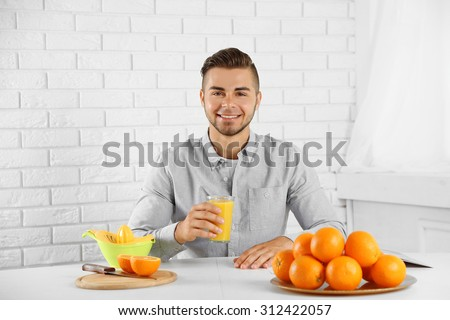 Young man having a table full of fresh oranges and juice - stock photo