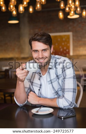 Young man having cup of coffee at the cafe - stock photo