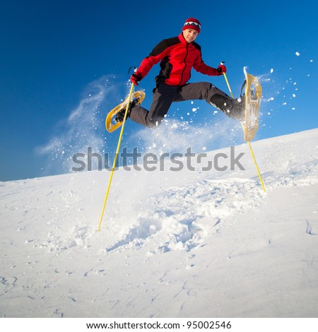 Young man having fun while snowshoeing outdoors on a lovely snowy winter day - stock photo