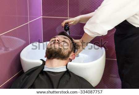 Young man having his hair washed in a hairdressing salon - stock photo