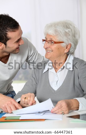 Young man helping elderly woman with paperwork - stock photo
