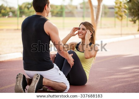 Young man helping his girlfriend do some crunches outdoors while working out together - stock photo