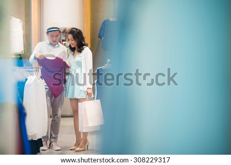 Young man helping his girlfriend to choose clothes in the boutique - stock photo