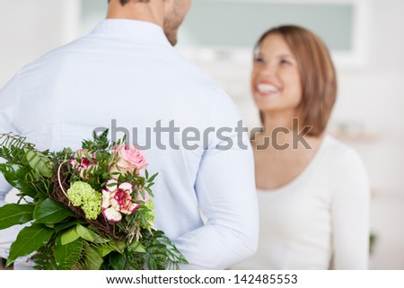 Young man hides a bouquet of flowers behind his back - stock photo