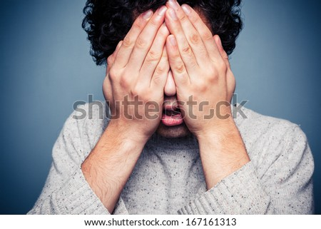 Young man hiding his head in his hands - stock photo