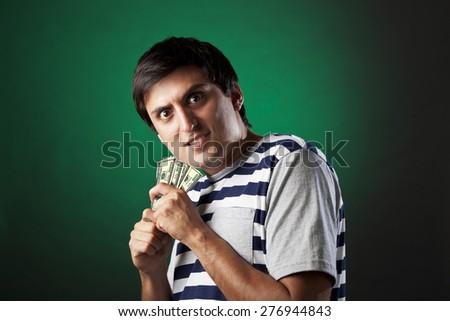 Young man hiding his money miser - stock photo