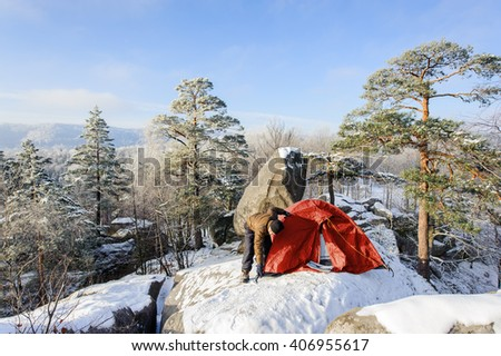 Young man hiker is putting up his red tent on a big rock at the winter mountain base camp on a cold sunny day. Winter camping. Winter hiking equipment. - stock photo