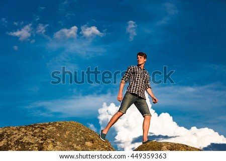 Young man hiking in front of blue sky - stock photo