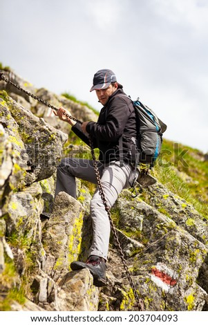 Young man hiking into the mountains in a spectacular landscape - stock photo
