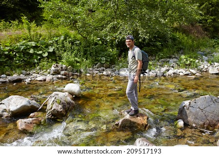 Young man hiking into the woods, crossing a river - stock photo