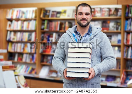 Young man hold books in the library - stock photo