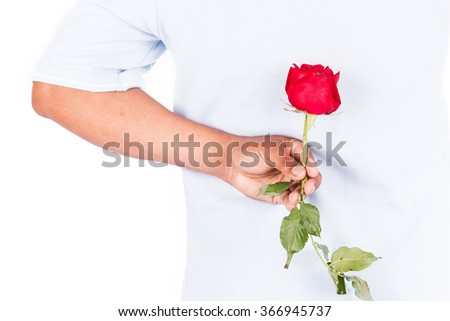 young man hold rose flower behind for surprise his wife - stock photo