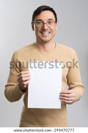 Young man holding a blank sheet isolated over gray - stock photo