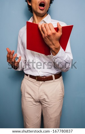 Young man holding a book and singing - stock photo