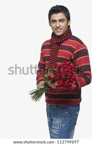 Young man holding a bouquet of roses - stock photo