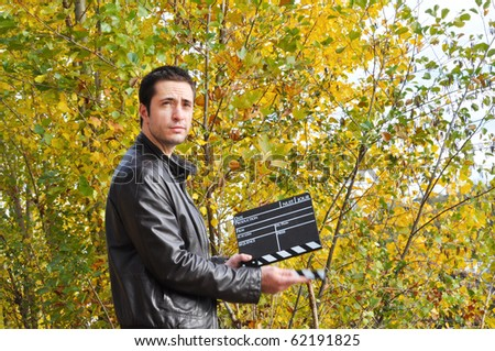 Young man holding a cinema clap - stock photo