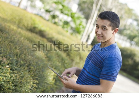Young man holding a digital tablet outdoors - stock photo