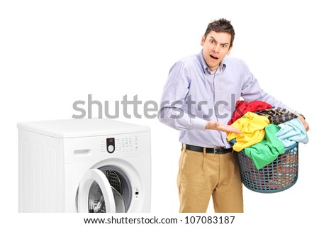 Young man holding a laundry basket and gesturing near a washing machine isolated on white background - stock photo