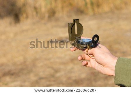 Young man holding a magnetic compass as he stands outdoors in the countryside using it for navigation and to find his geographic location - stock photo