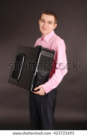 Young man holding a pc black background with soft shadow - stock photo