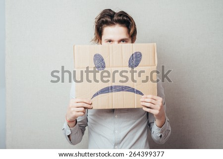 young man holding a picture of a cheerful smiley - stock photo