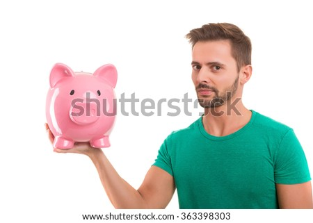 Young man holding a piggy-bank - money concept - stock photo
