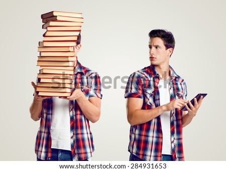 Young man holding a pile of books and a tablet - stock photo