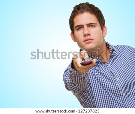 Young Man Holding a Remote Control against a blue background - stock photo