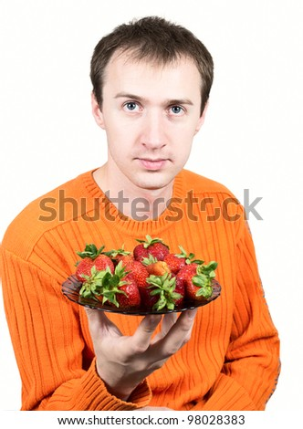 Young man holding a strawberry isolated on white background. - stock photo