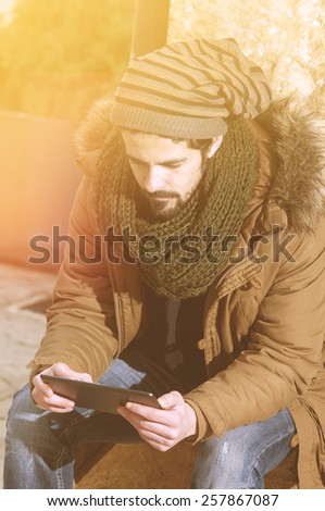 young man holding a tab�²et note pad with his right hand in an outdoor urban setting instagram filte applied - stock photo