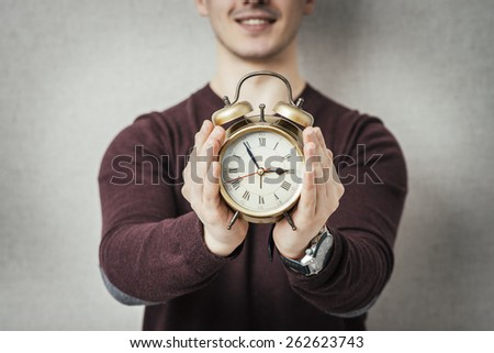 young man holding an alarm clock - stock photo