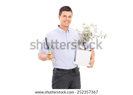 Young man holding an olive tree plant and a spade isolated on white background - stock photo