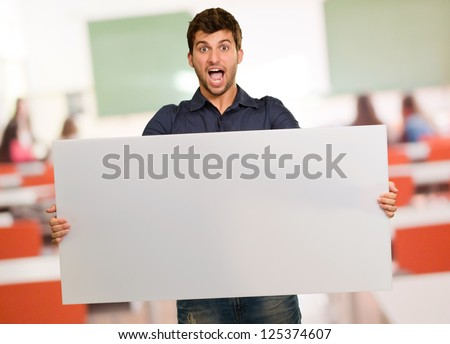 Young Man Holding Banner Gesturing, Indoors - stock photo
