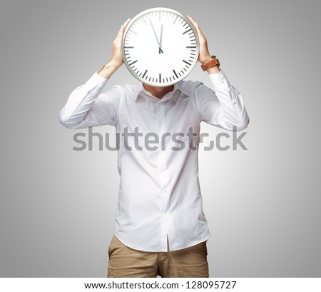 Young Man Holding Big Clock Covering His Face On Gray Background - stock photo