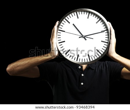 young man holding big clock covering his face over black background - stock photo