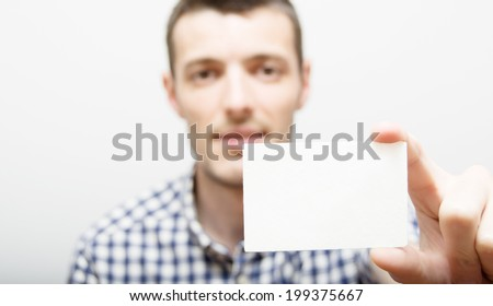 Young man holding blank visiting card - stock photo