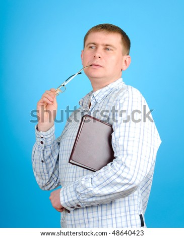 Young man holding book an glass on blue background - stock photo