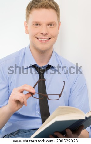 young man holding book and smiling. handsome guy with glasses on white background - stock photo