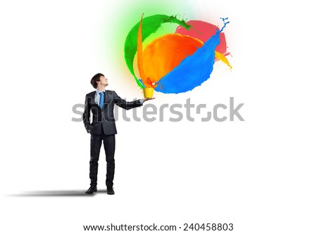 Young man holding bucket and colorful paint splashes - stock photo