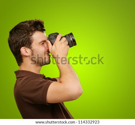 Young Man Holding Camera On Green Background - stock photo