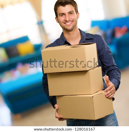 Young Man Holding Card boxes, Indoors - stock photo