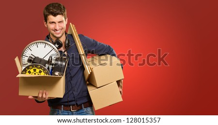 Young Man Holding Cardboxes Gesturing On Red Background - stock photo