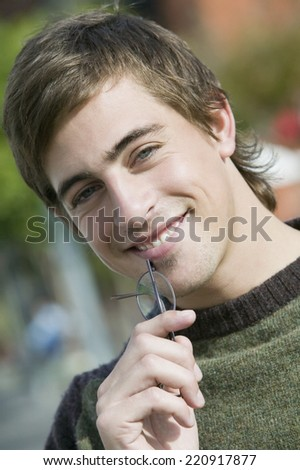 Young man holding eyeglasses - stock photo
