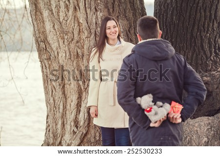 Young man holding gifts for girlfriend behind his back to surprise her. - stock photo