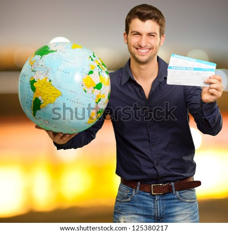 Young Man Holding Globe And Boarding Pass, Outdoor - stock photo