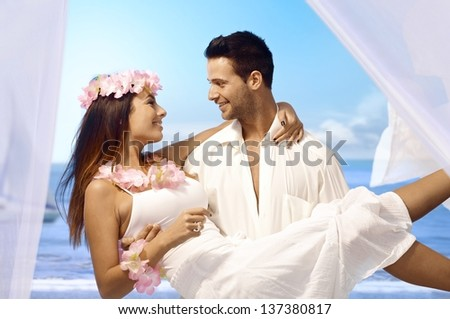 Young man holding happy bride in arms after exotic wedding on tropical island. - stock photo