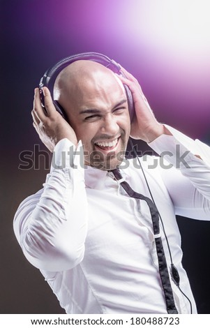 Young man holding his headphone and having fun with music - stock photo